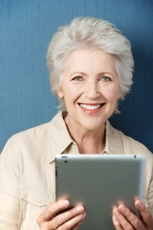 Vertical portrait of a Caucasian senior good looking woman smiling and holding a PC tablet